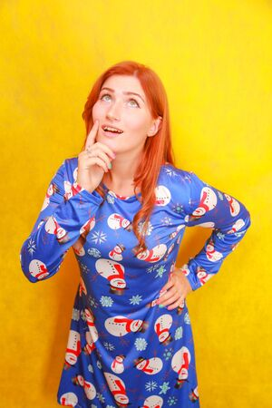 Careless dreamy attractive lady with red hair wearing blue funny christmas dress on yellow bright studio background
