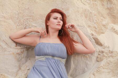 Young beautiful Caucasian woman in evening shiffon dress posing in desert landscape with sand.