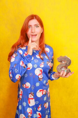 pretty redheaded girl in blue funny christmas dress with coin money box on yellow background. woman preparing to new year and ready to buy presents and gifts.