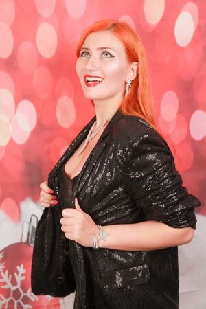 happy smiling redhead girl with red lipstick on christmas background Stockfoto