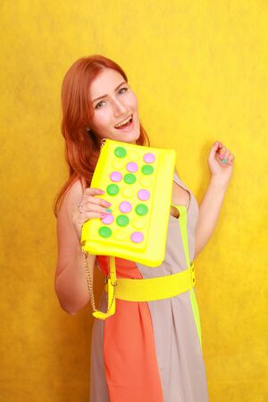 pretty redheaded girl in bright summer dress with yellow bright leather bag Stock fotó