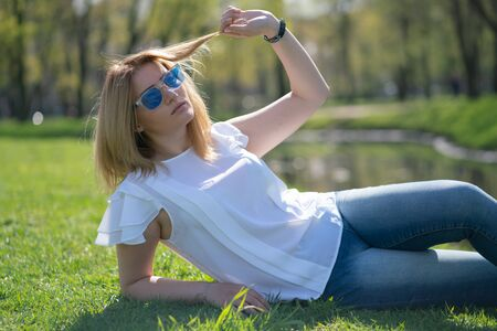 pretty woman relaxing by walking in the city park in jeans outfit