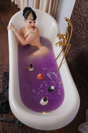 fille gothique en bonne santé aux cheveux noirs dans la luxueuse salle de bain marron avec de l'eau salée violette Banque d'images