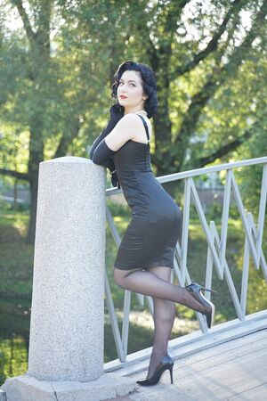 retro woman in classic pin up dress on the bridge in the city park