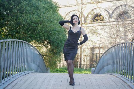retro woman in classic pin up dress on the bridge in the city park Banco de Imagens