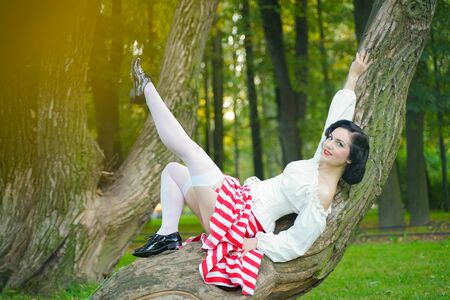 Close-up of a happy young pin up girl posing with tree at the park
