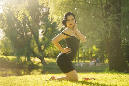 Beautiful young woman with pin-up make-up and hairstyle posing in the summer city park