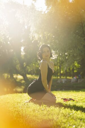 Beautiful young woman with pin-up make-up and hairstyle posing in the summer city park Фото со стока