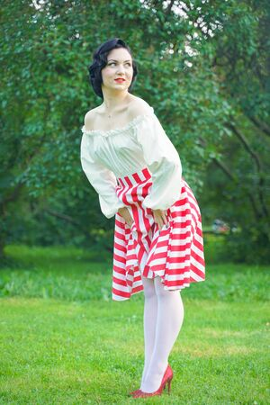 Vintage portrait of a woman in retro white and red dress in the city park Stock Photo