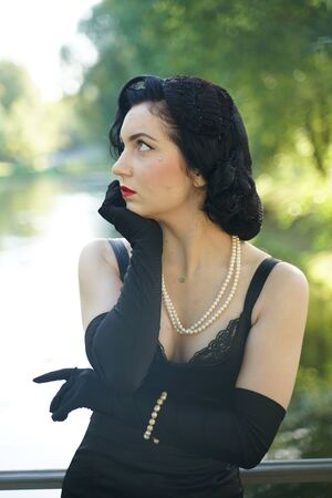 Portrait of beautiful pinup girl in black dress outdoor on the nature