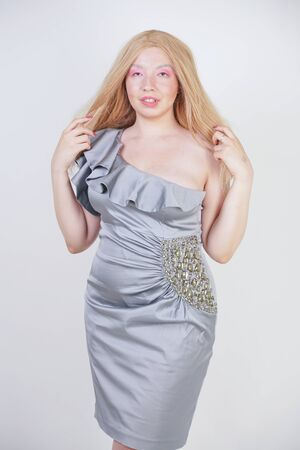 hot fashionable blonde mix raced woman in trendy party dress on plus size body on white studio background Standard-Bild