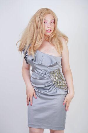 heiße modische blonde Mix-Racing-Frau in trendigem Partykleid auf Plus-Size-Körper auf weißem Studiohintergrund