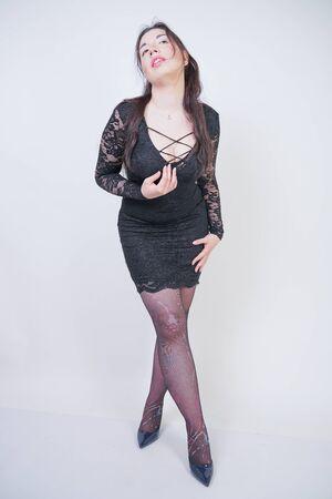 hübsches Mix-Race-Girl in Übergröße in elegantem Midikleid aus schwarzer Spitze auf weißem Studiohintergrund Standard-Bild