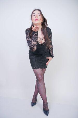hübsches Mix-Race-Girl in Übergröße in elegantem Midikleid aus schwarzer Spitze auf weißem Studiohintergrund
