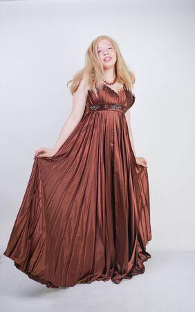 Süße Mix-Rennfrau in Übergröße in langen, formellen Kleidern auf weißem Studiohintergrund, die allein mit ganzer Körperlänge steht Standard-Bild