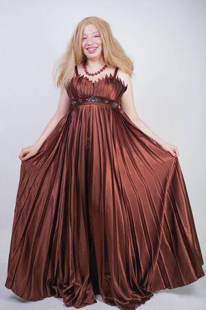 Süße Mix-Rennfrau in Übergröße in langen, formellen Kleidern auf weißem Studiohintergrund, die allein mit ganzer Körperlänge steht