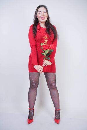 hübsches Mix-Race-Girl in Übergröße in elegantem Midikleid auf weißem Studiohintergrund mit Rose