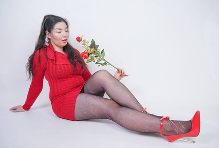 pretty mix raced plus size girl in elegant red midi dress sitting on white studio background with red rose Standard-Bild
