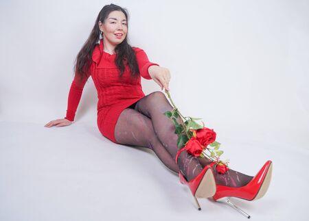 hübsches, gemischtes Mädchen in Übergröße in elegantem rotem Midikleid, das auf weißem Studiohintergrund mit roter Rose sitzt