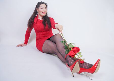 pretty mix raced plus size girl in elegant red midi dress sitting on white studio background with red rose