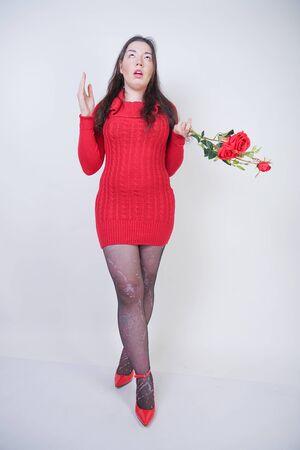 Hübsches Mix-Race-Mädchen in Übergröße in elegantem Midi-Rotkleid hasst Blumenrosen auf weißem Studiohintergrund