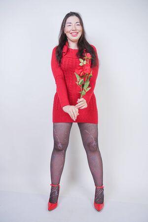 hübsches Mix-Race-Girl in Übergröße in elegantem Midikleid auf weißem Studiohintergrund mit Rose Standard-Bild