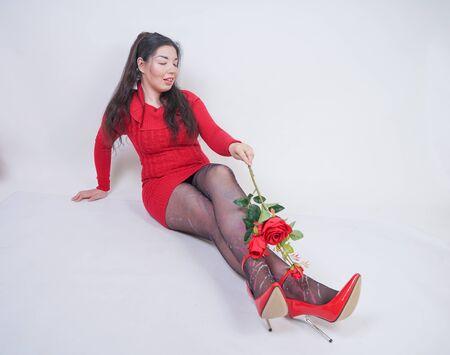 hübsches, gemischtes Mädchen in Übergröße in elegantem rotem Midikleid, das auf weißem Studiohintergrund mit roter Rose sitzt Standard-Bild