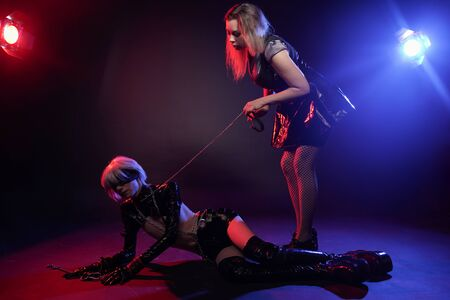 couple of lovers have play in neon light on black background. woman mistress and her slim anime slave man in the studio.