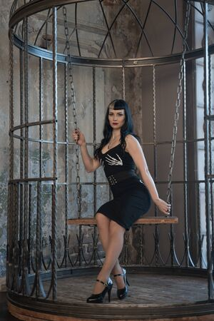 Chica gótica sexy en vestido negro ajustado detrás de la gran jaula haciéndose pasar por víctima de la esclavitud sola Foto de archivo