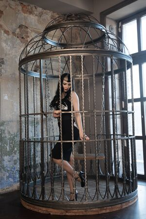 Sexy gothic girl in tight black dress behind the big cage posing as slavery victim alone Stock Photo