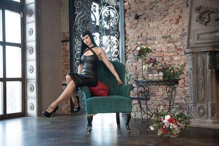 Gothic slim caucasian girl in black tight dress posing in her room