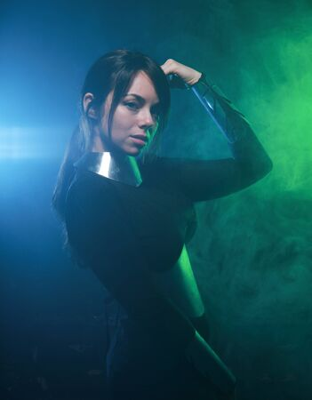 futuristic fashion model wearing black and silver clothes and standing in the colorful blue and green smoke Фото со стока