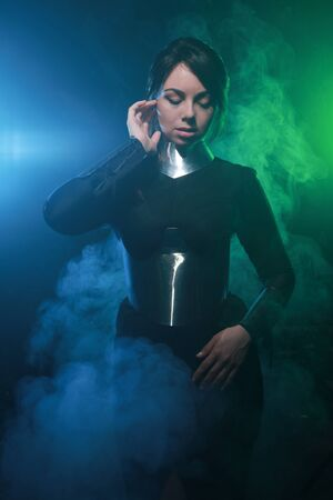 futuristic fashion model wearing black and silver clothes and standing in the colorful blue and green smoke