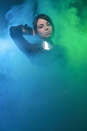 futuristic fashion model wearing black and silver clothes and standing in the colorful blue and green smoke 免版税图像