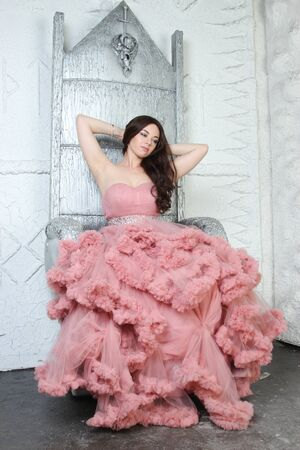 Portrait of fashionable young beauty girl in big long evening pink dress Фото со стока