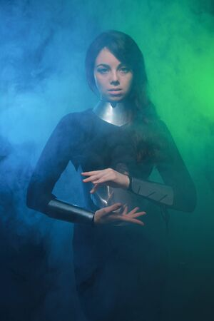 futuristic fashion model wearing black and silver clothes and standing in the colorful blue and green smoke Banque d'images