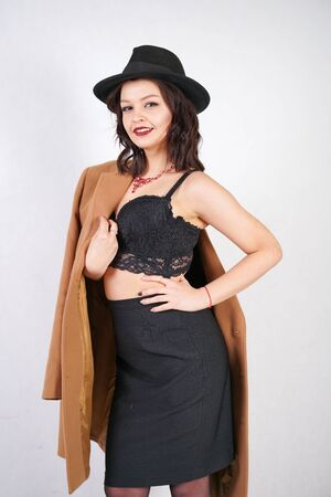 fashion woman in trendy mans hat and classic jacket on white studio background. retro lady in black outfit standing alone.