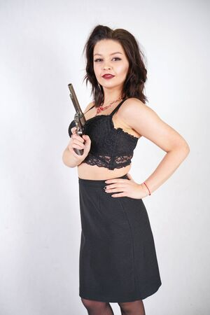 Sexy young happy woman with gun on white studio background alone