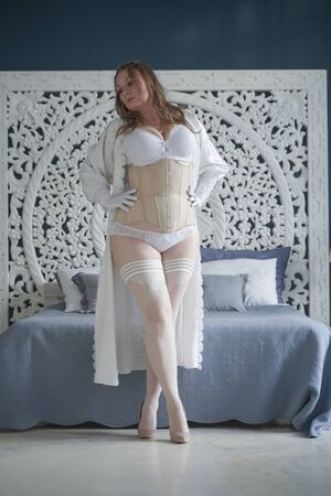 sexual plus size bride girl in white lingerie in the bedroom alone. chubby woman in lace underwear with corset and stockings alone Stok Fotoğraf