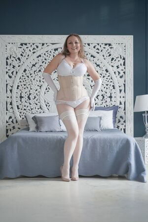 sexual plus size bride girl in white lingerie in the bedroom alone. chubby woman in lace underwear with corset and stockings alone Banco de Imagens