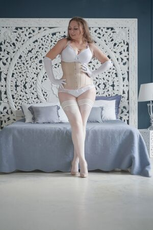 sexual plus size bride girl in white lingerie in the bedroom alone. chubby woman in lace underwear with corset and stockings alone Фото со стока