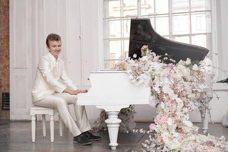 Jeune homme adolescent avec un grand piano à queue blanc à l'intérieur seul aime la musique Banque d'images