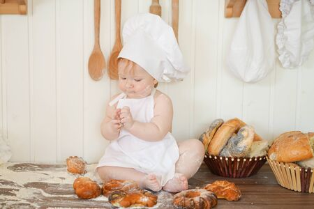 little baker child in chef hat at kitchen table alone