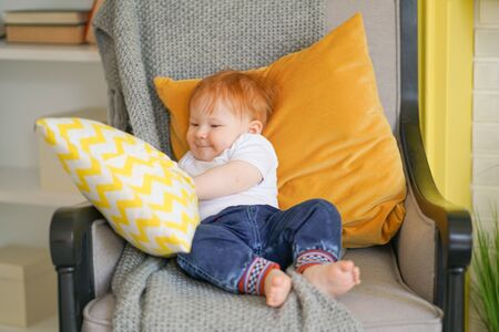 small child sits in a chair and holds a pillow in his hands.