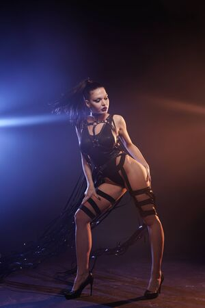 beautiful mix race slender muscular dancer girl posing in a black swimsuit with leather harness with videotape tapes