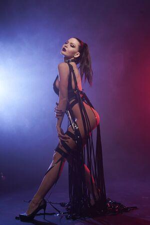 Young woman dancer posing in the smoke