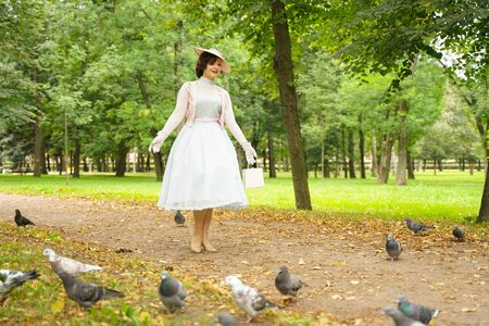 Portrait of pin up young woman in vintage dress and retro hat walking
