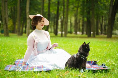 Pretty vintage woman walking with her black cat maine coon in the park