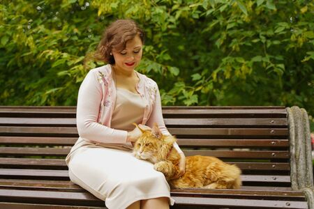 pretty girls walks with her big cat outdoor. concept of love and happy hug with pet.