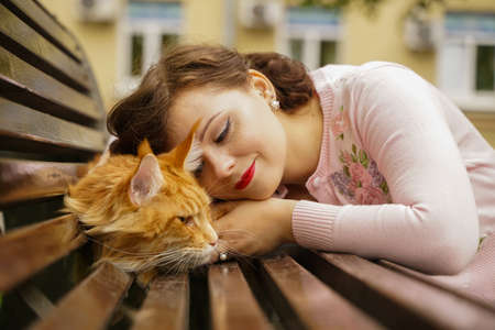 big red maine coon cat is scary and sad. young owner woman hugs and strokes her orange pet in stress from first walk outdoor.